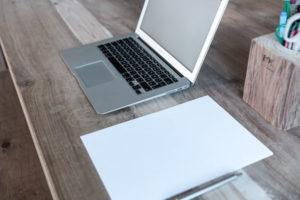 ノートパソコンとノートとペンが机上に置いてある