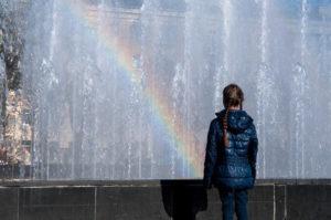 噴水に架かる虹を見ている女の子